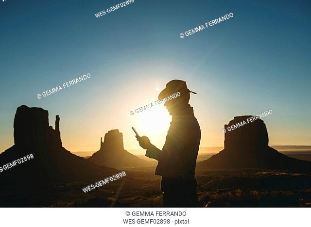 USA, Utah, Monument Valley, silhouette of man with cowboy hat looking at mobile phone at sunrise