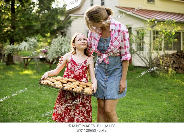 Baking homemade cookies. A young girl holding a tray of fresh baked cookies, and an adult woman leaning down to praise her