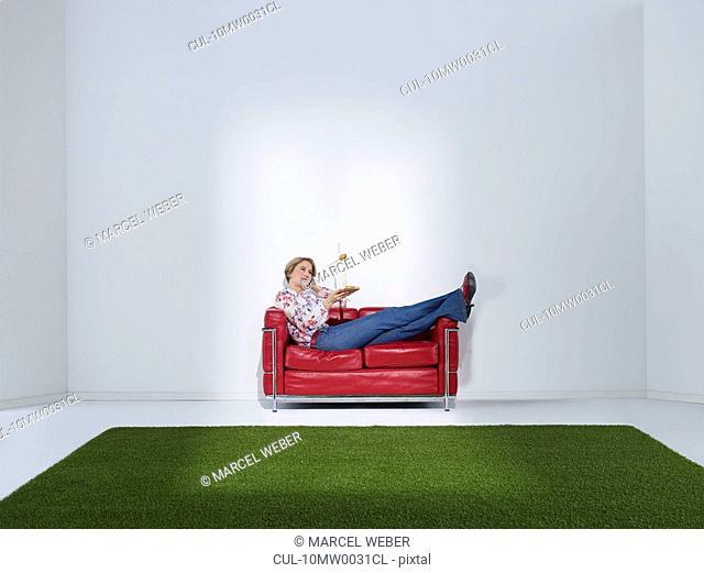 Woman laying on sofa with windwheel