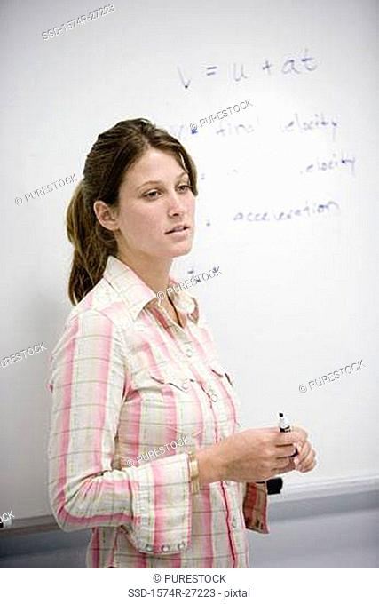 Female student standing in front of a white board in the classroom
