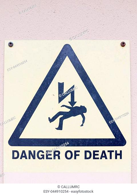 a white yellow and black close up sign on the wall saying danger of death with electric bolt and dead man in triangle safety warning electrics electrified uk...
