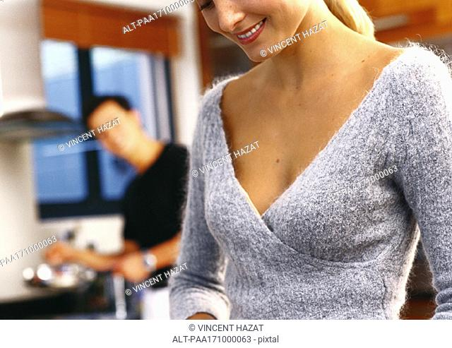 In kitchen, woman smiling, man in blurred background, close-up