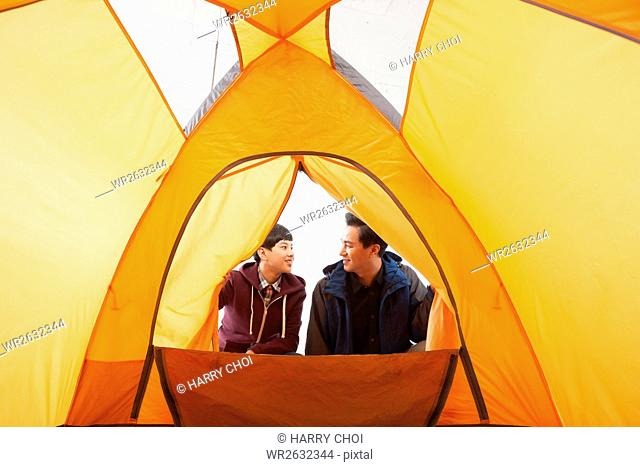 Smiling father and son in a tent face to face