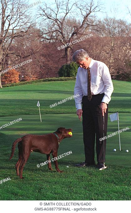President William Jefferson Clinton and Buddy the Dog playing on the putting green on the south lawn of the White House, February 10, 1998