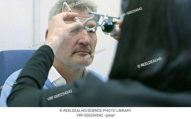 Patient wearing frames during an eye test with an optician. The frames allow the optician to changes lenses during the test