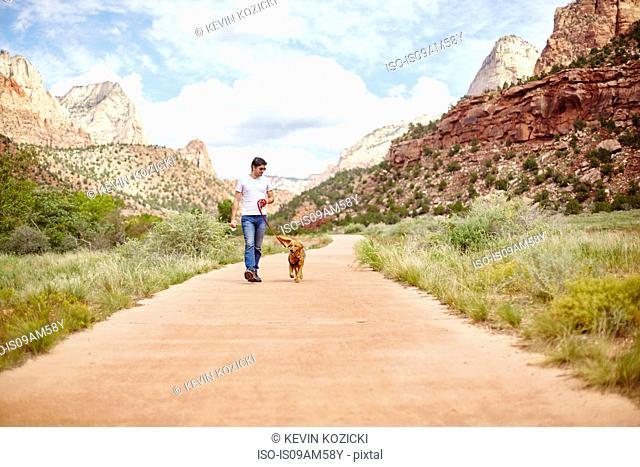 Man walking dog, Zion, Utah, USA