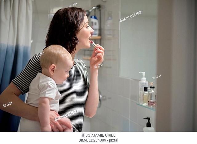Caucasian mother holding baby son while applying lipstick in mirror
