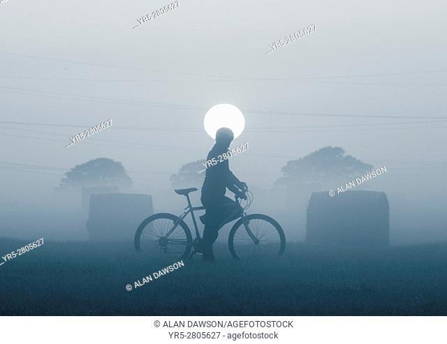 Female mountain biker near Hay bales at sunrise in early morning mist near Billingham, north east England, United Kingdom. United Kingdom