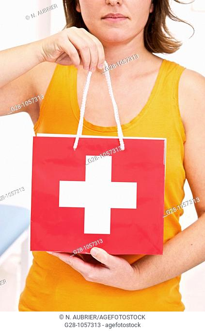 young woman ( face invisible ) holding a medical red bag with a white cross