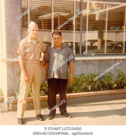 American soldier in uniform standing with a Vietnamese man in front of a hotel in Vietnam during the Vietnam War, 1968. ()