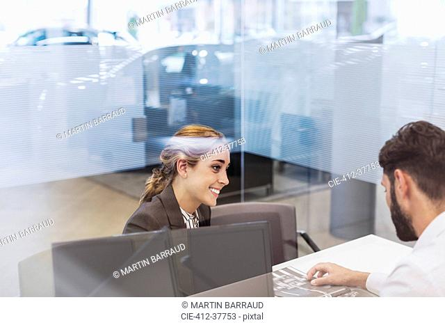 Smiling car saleswoman talking to male customer in car dealership office
