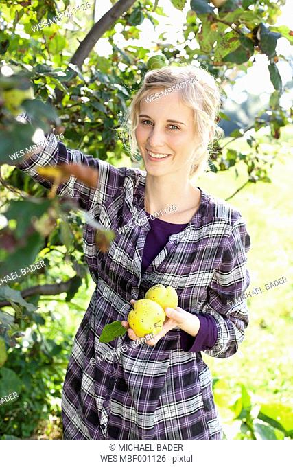 Germany, Saxony, Young woman holding vegetable, smiling, portrait