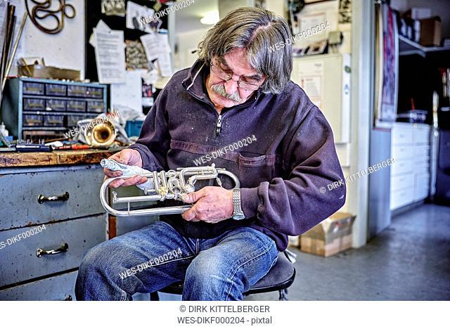 Instrument maker cleaning trumpet in workshop