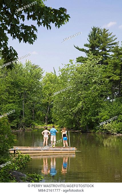 A family of four standing on a dock observing a ball in the Mille-Iles river, Ile Saint-Jean, Terrebonne, Lanaudiere, Quebec, Canada