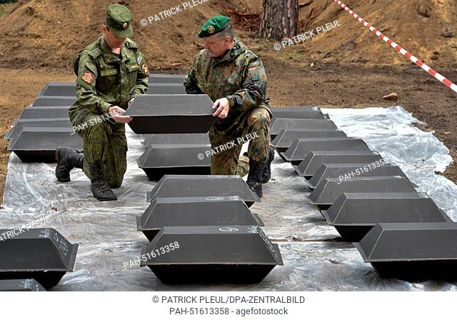 Major of the Russian army Sergey Rumyantsev (L) and Lieutenant-Colonel of the German army Carsten Heldt carry a small coffin containing the mortal remains of...