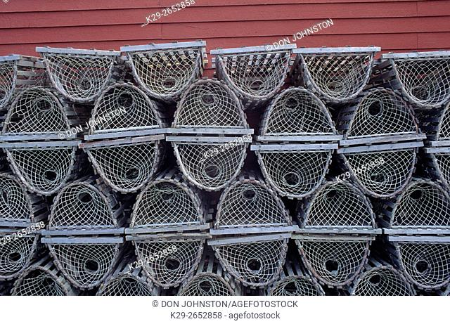 Lobster traps stacked against red wall, Gros Morne NP, NL, Canada