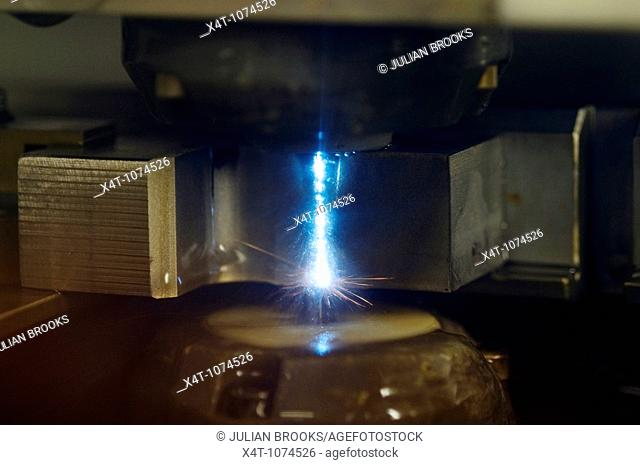 close up of a wire erosion machine shaping a piece of steel, precision engineering  Water cooling system turned off  Sparks clearly visible