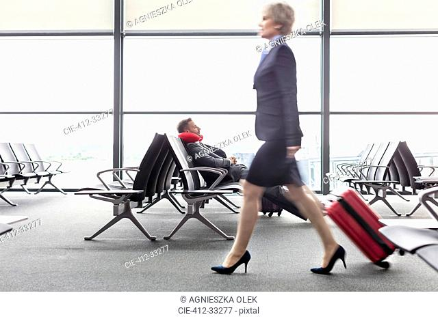 Businesswoman pulling suitcase past resting businessman with neck pillow in airport departure area