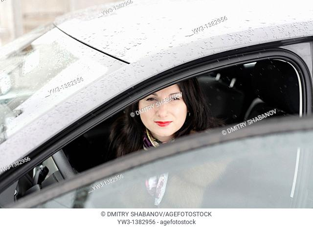 The girl in a fur coat sitting in the car