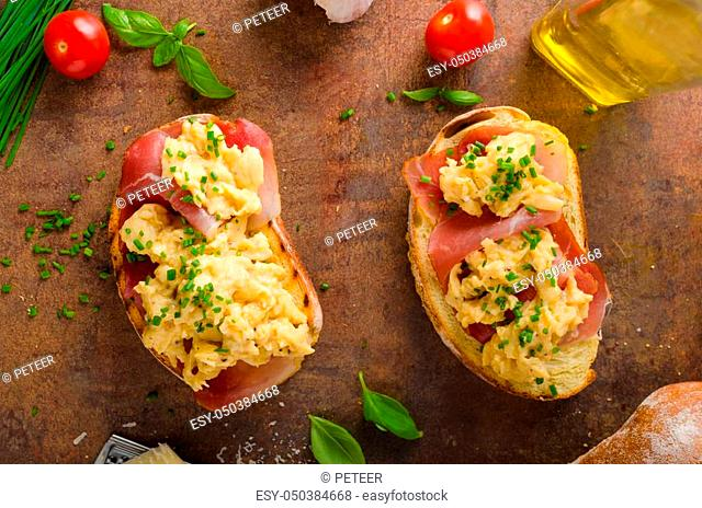 Delicious toasted bread with scrambled eggs, topped with chive and tomatoes