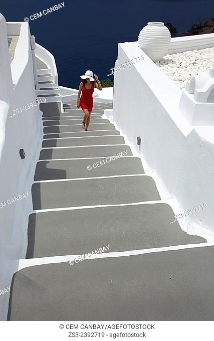 Woman climbing up the stairs in Oia town, Santorini, Cyclades Islands, Greek Islands, Greece, Europe