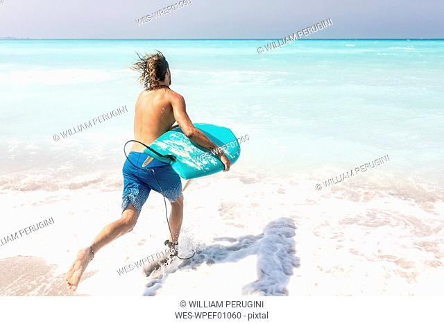Young man running into ghe sea, carrying his surfboard