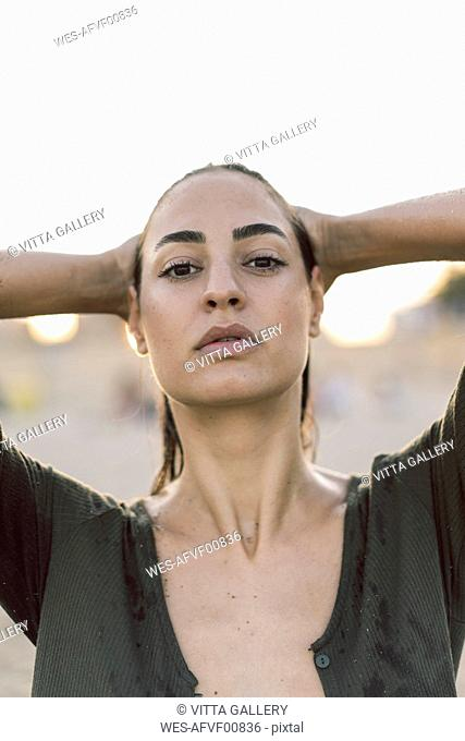 Beautiful woman on the beach at sunset with wet hair