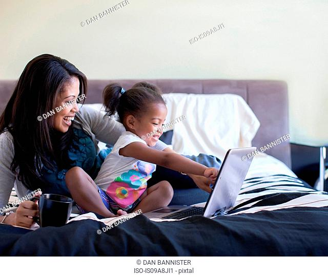 Mother and daughter using laptop on bed
