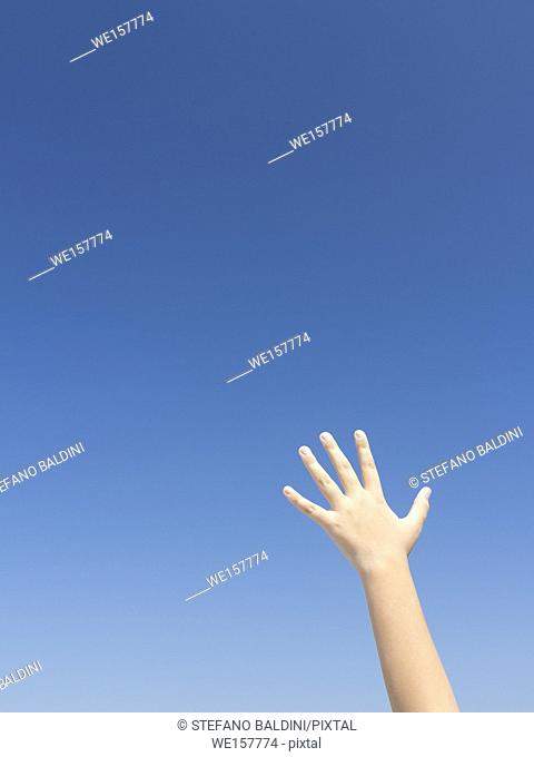 Young girl's hand against blue sky
