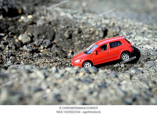 Pothole in a road with miniature car