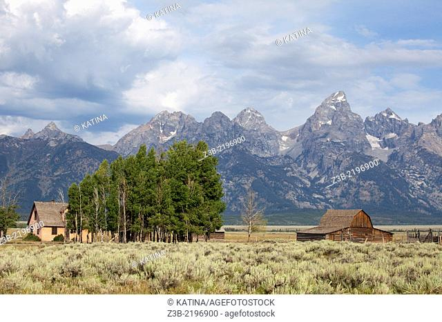 Barn and home with Grand Tetons in the background, Grand Teton National Park, Wyoming, USA