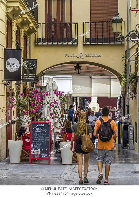 Two people walking towards Plaça Redona (Plaza Redonda), a pedestrianised area shaped in a circle containing boutique stalls, shops and tapas bars, Valencia