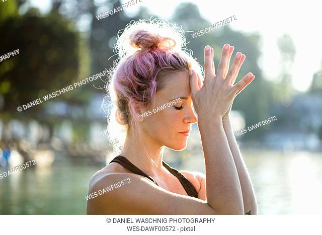 Woman with dyed hair meditating at a lake