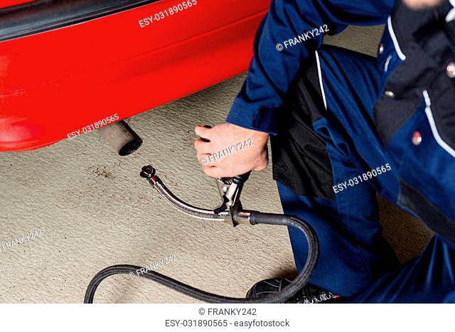 A mechanic is applying a diagnostic sensor to the ehaust of a red car, measuring the composition and substances in the exhaust fumes in a garage- given the...