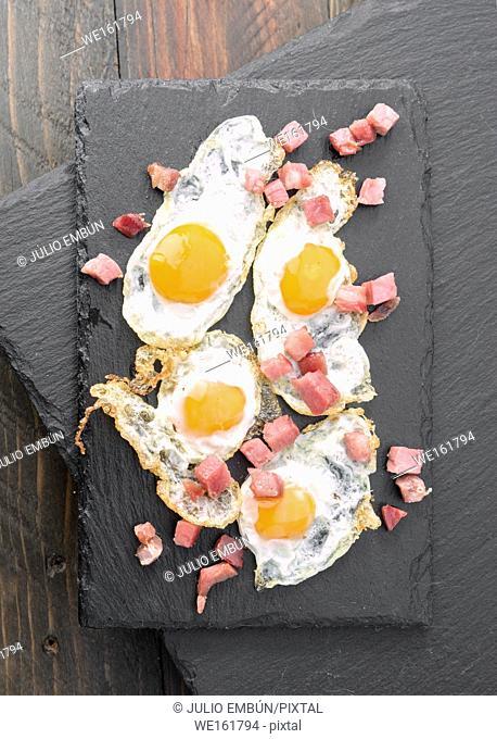 fried quail egg with baked ham on black stone