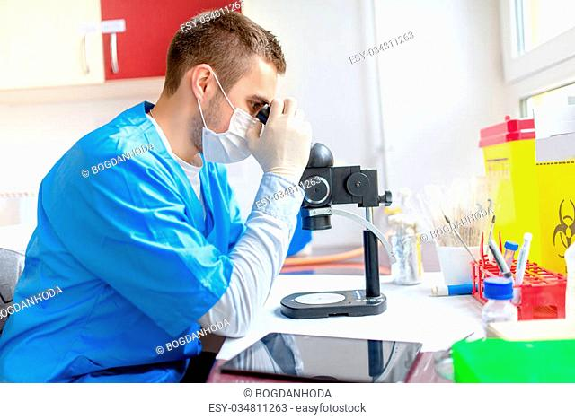 male chemist working with microscope in laboratory