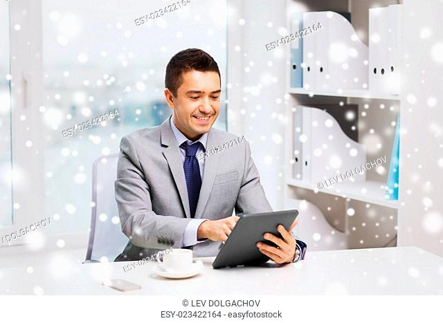 business, education, people and technology concept - smiling businessman with tablet pc computer and coffee in office over snow effect
