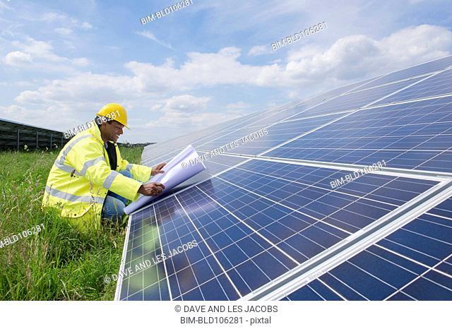 Mixed race man with blueprints near solar panels