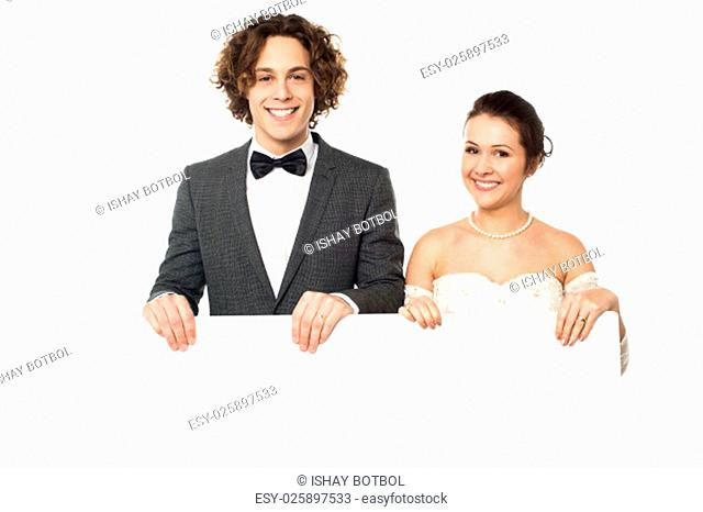 Newly-wed couple displaying a blank poster