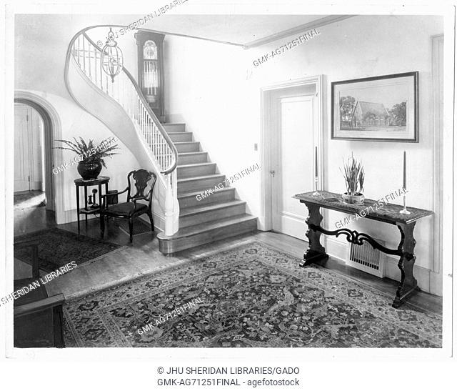 The foyer of a Guilford house, there is a rug in the foreground and a wooden staircase in the background, there are some furniture pieces in the room like a...