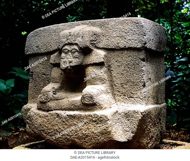 Priest with his head covered by a jaguar tiara while carrying a dead child, from the stone Altar 3 in Villahermosa (Mexico)