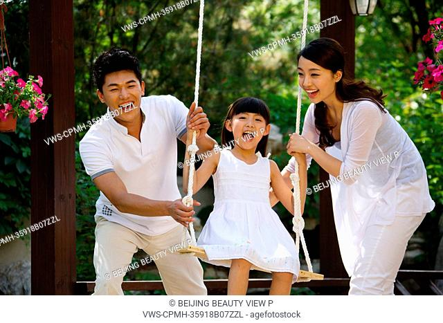 Girl playing swing with her parents