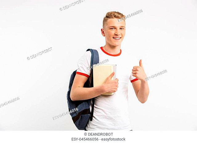 Image of happy male student wearing backpack smiling and showing thumb up while holding books isolated over white background