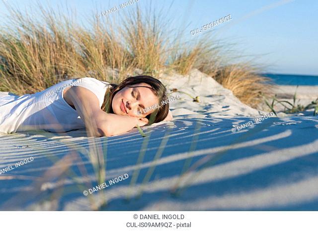 Mid adult woman lying on soft sandy beach