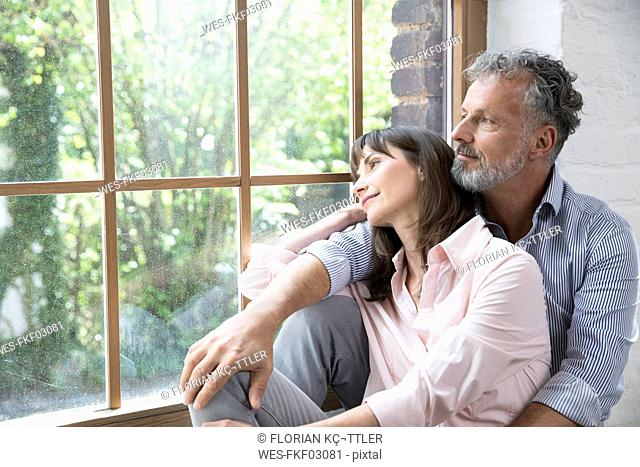 Mature couple sitting on window sill, looking out of window
