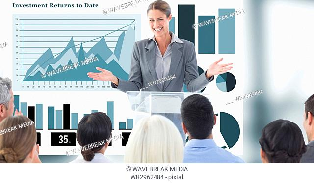 Businesswoman giving presentation to colleagues with graphs in background