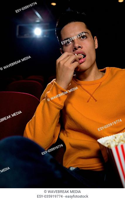 Man having popcorn while watching movie in theatre