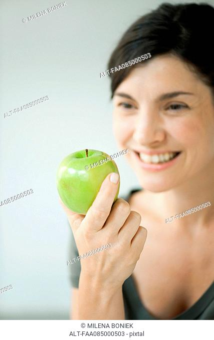 Woman holding green apple