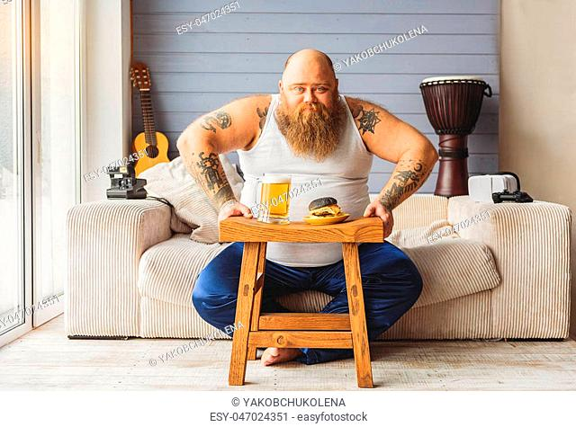 Brutal fat man is ready to drink beer with sandwich. He is sitting on sofa at home and looking at camera with confidence