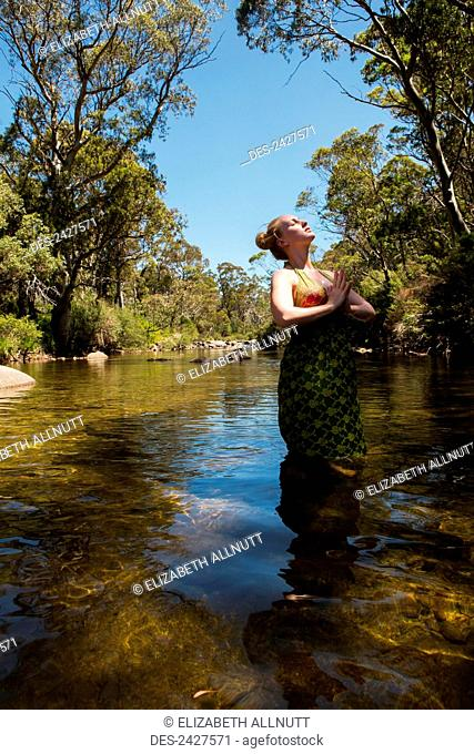 Young woman standing in a creek doing yoga poses; Threadbo, New South Wales, Australia